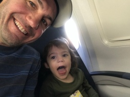G and Dad on the plane, 3 rows behind us.